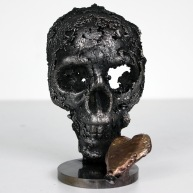 Sculpture représentant un coeur en bronze sur une tête de mort en dentelle d'acier Un coeur de vanité