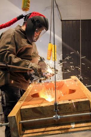 Photo du sculpteur Philippe Buil entrain de sculpter dans son atelier de la Galerie Art Pluriel à Saint-Etienne