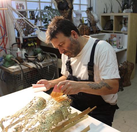 Le sculpteur Philippe Buil entrain de poser des feuilles d'or 24 carats sur une de ses sculptures